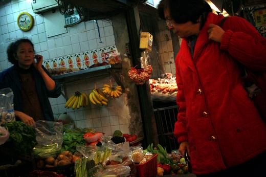 商店街で野菜を買うおばさん
